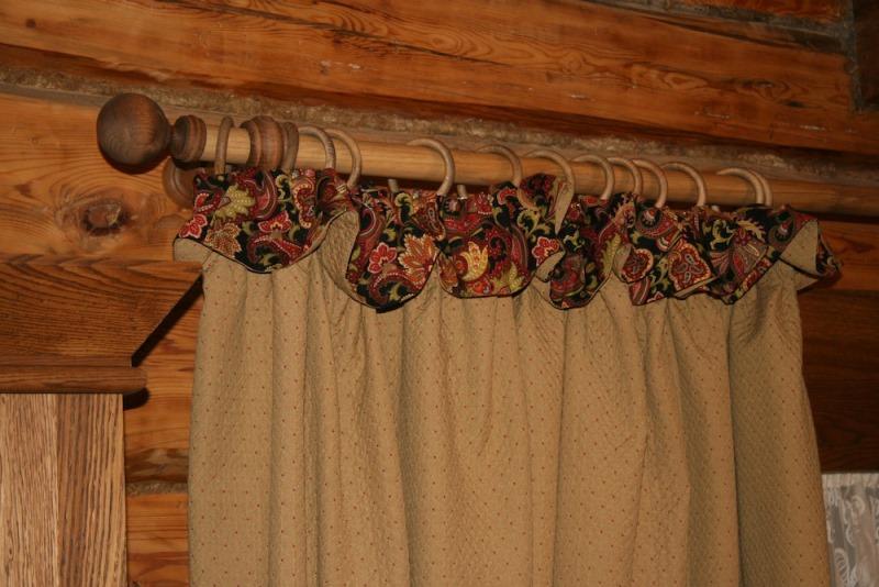Декорирование просторных комнат со стенами, выполненными из дерева, подразумевает использование традиционных карнизов и тканевых полотен самих штор