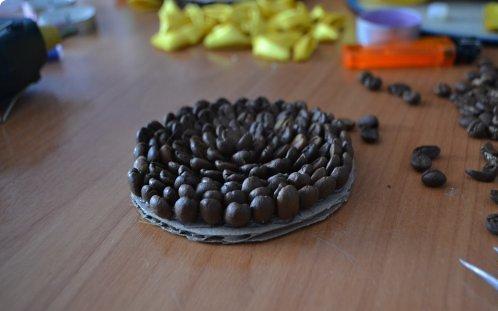 Темные блестящие кофейные зерна имитируют семечки, а из яркого желтого атласа изготовляются лепестки