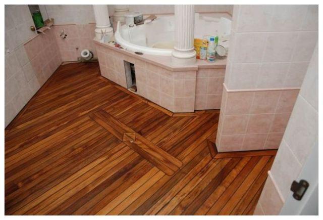 Пол в ванной комнате из дерева выглядит красиво, но отличается очень сложной установкой