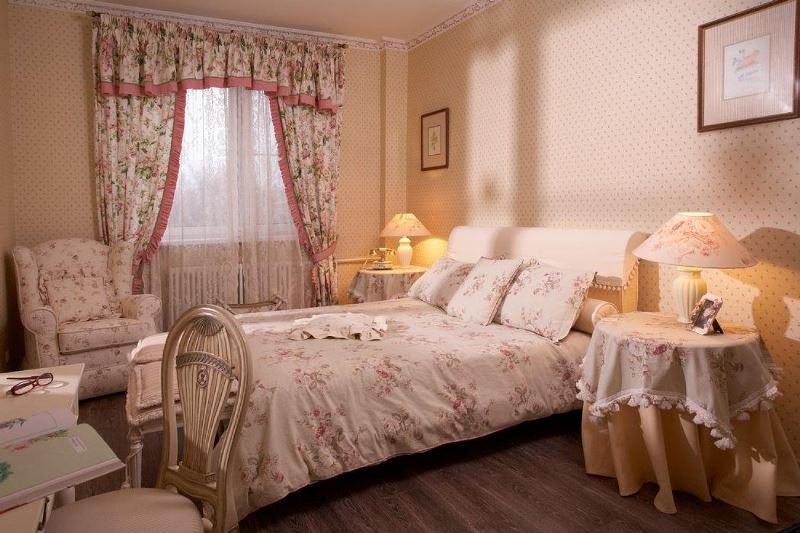 Стиль прованс в спальне можно поддержать полупрозрачными занавесками, расписанными цветочными изображениями на светлых полотнах